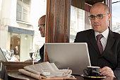 Mature businessman sitting  outside cafe using laptop