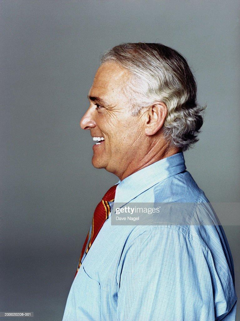 Mature businessman smiling, profile