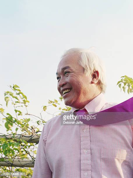 Mature businessman smiling, tie flying in wind,  close up