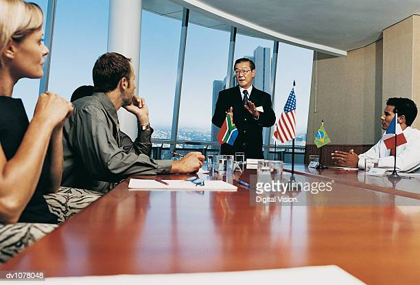 Mature Businessman Standing at a Conference Table With Other Business Executives Applauding Him