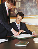Mature businessman standing by colleague, pointing at papers on desk