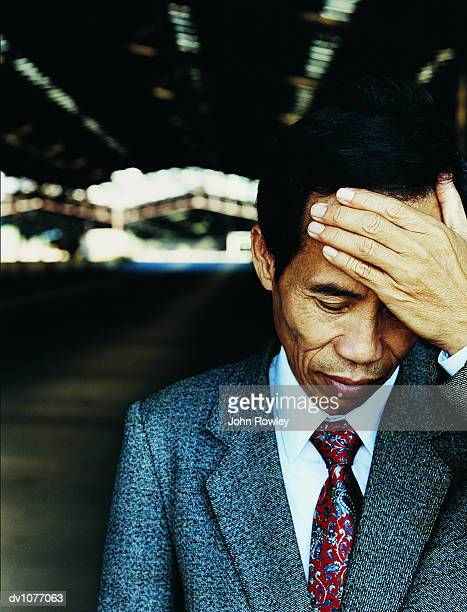 Mature Businessman Standing in a Factory and Looking Down With His Hand on His Head