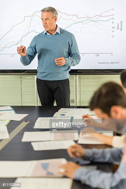 Mature businessman standing in front of a graph talking
