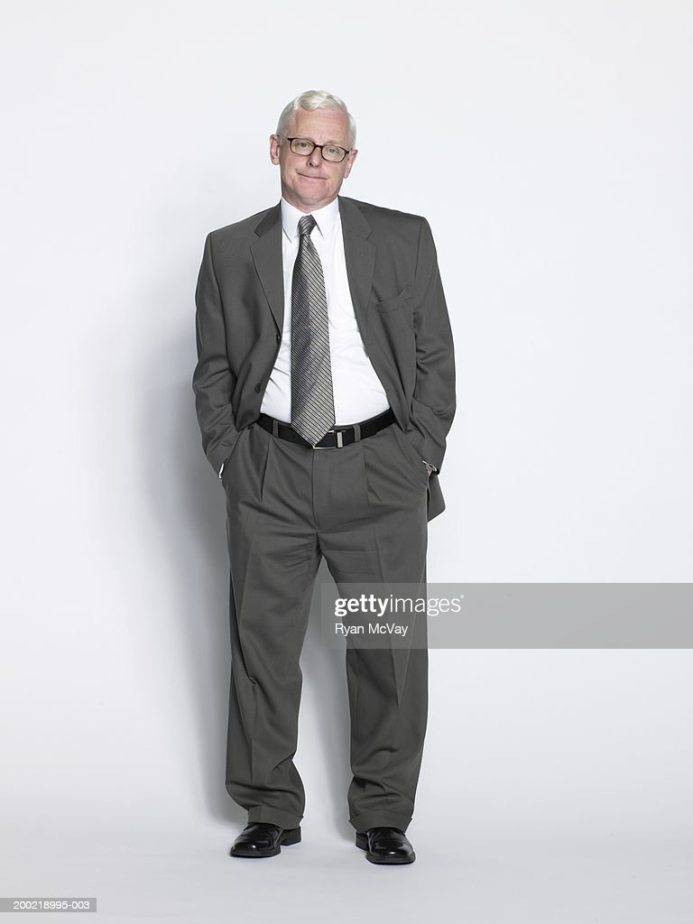 Mature businessman standing with hands in pockets, portrait : Stock Photo