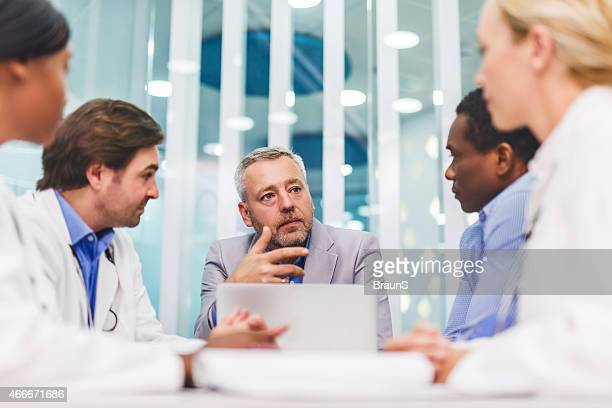 Mature businessman talking on a meeting with doctors.