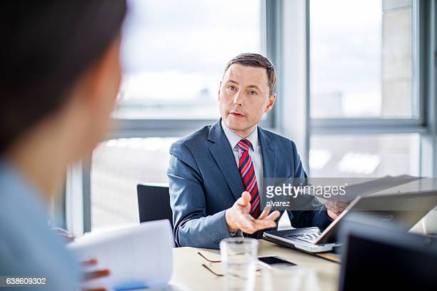 Mature businessman talking with colleague in meeting