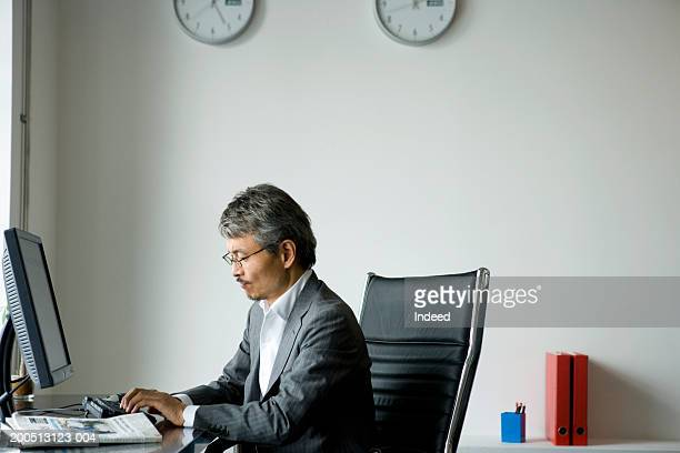 Mature businessman typing on keyboard, side view