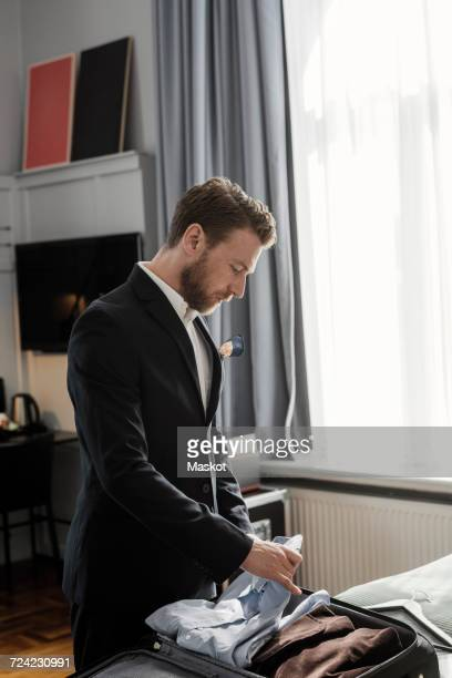 Mature businessman unpacking luggage in hotel room