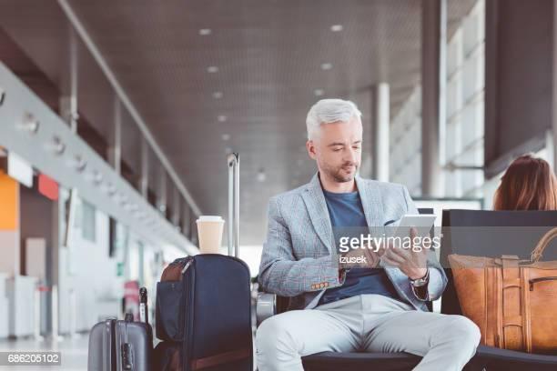Reife Geschäftsmann mit einem digitalen Tablet im Wartebereich des Flughafens