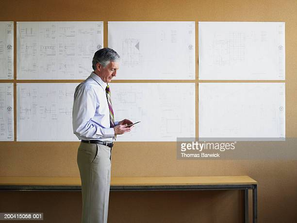 Mature businessman using cell phone, blueprints on wall in background