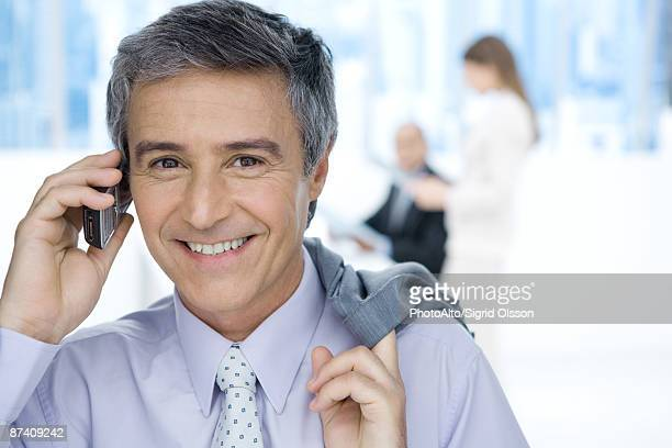 Mature businessman using cell phone in office, holding jacket over shoulder, smiling at camera