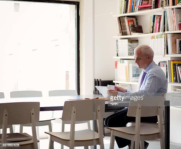 Mature businessman using digital tablet in office.