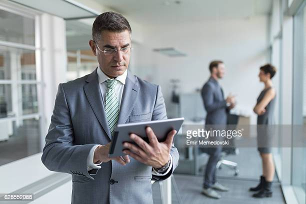 Mature businessman using digital tablet in the office