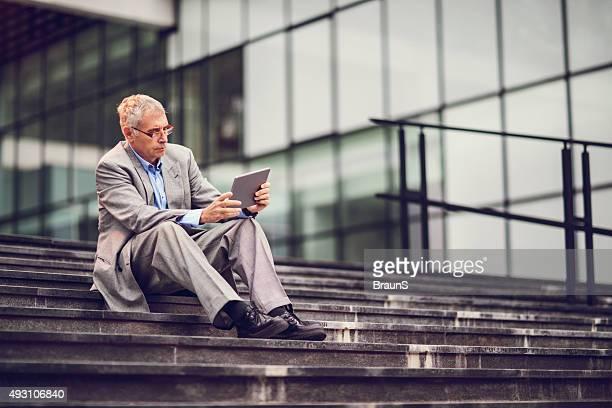 Reifer Geschäftsmann mit digitalen tablet, während Sie sich auf der Treppe