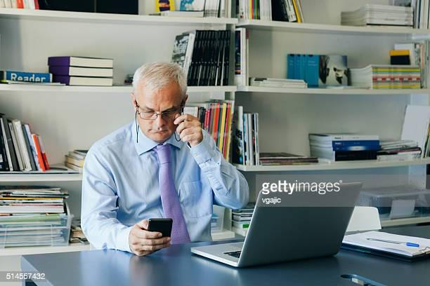 Reifer Geschäftsmann mit seinem Smartphone im Büro.