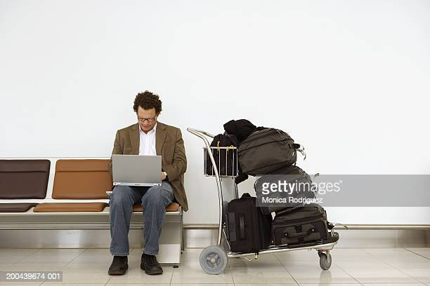 Mature businessman using laptop computer in airport