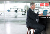 Mature businessman using laptop computer in airport, side view