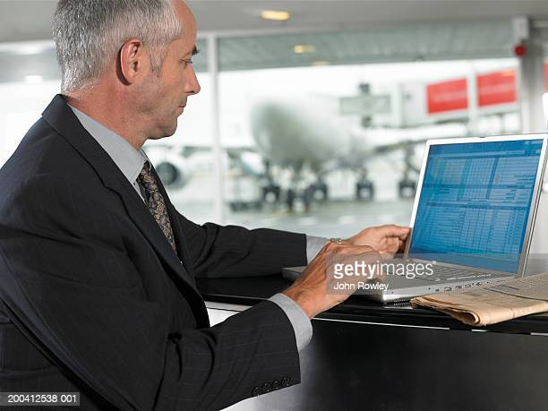 Mature businessman using laptop in airport, side view, close-up
