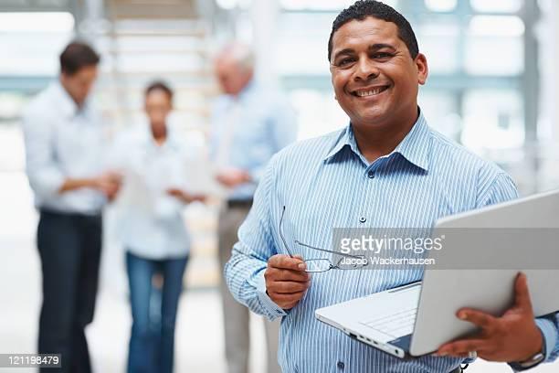 Empresário maduro usando laptop com executivos na parte de trás