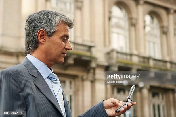 携帯電話を使用して大人のビジネスマン、クローズアップ、サイドの眺め