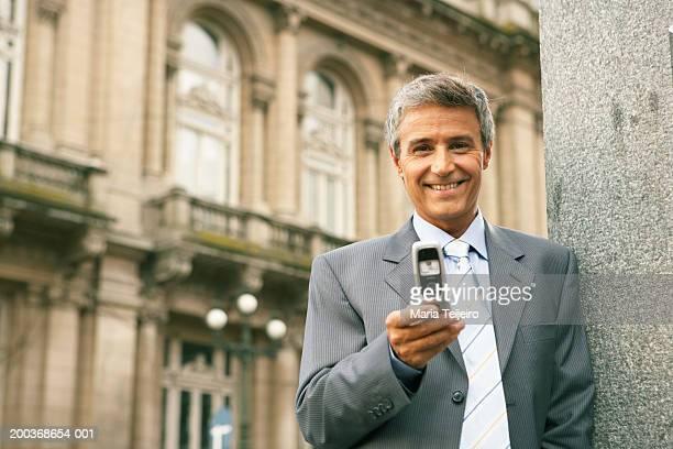 Mature businessman using mobile phone, smiling, portrait