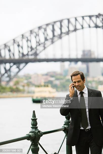 Mature businessman using mobile phone, Sydney Harbour, Australia