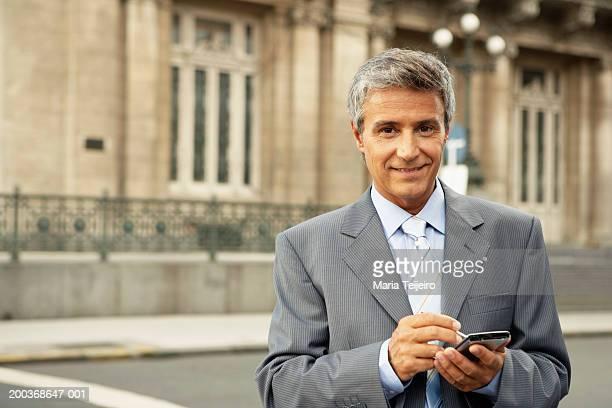 Mature businessman using palm pilot, smiling, portrait