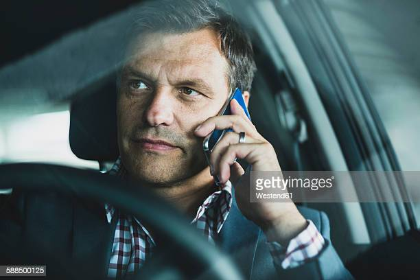 Mature businessman using smart phone in the car