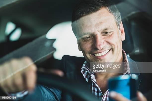Mature businessman using smart phone in the car