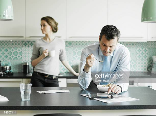 Mature businessman using tablet over breakfast in kitchen