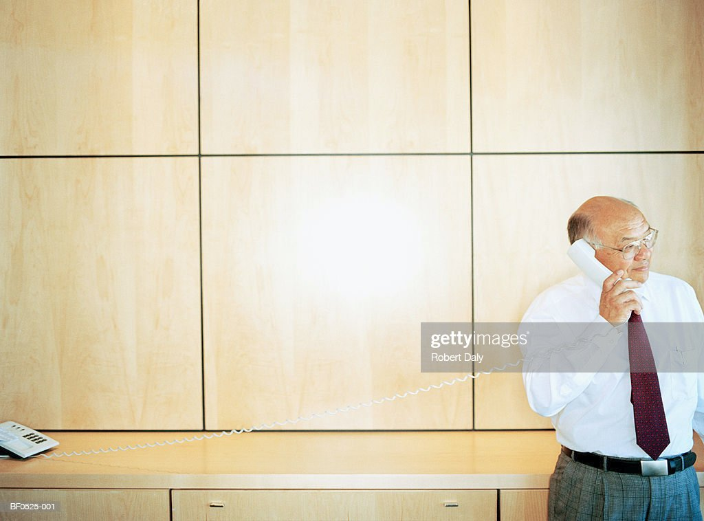 Mature businessman using telephone : Stock Photo