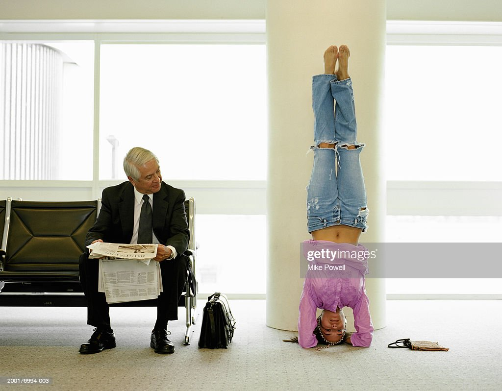 Mature businessman watching young woman doing yoga in airport lounge : Stock Photo