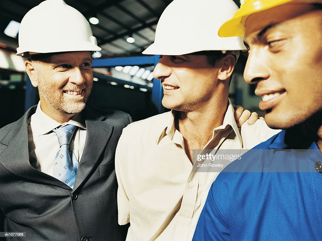 Mature Businessman Wearing a Hard Hat Thanking Two Factory Workers : Stock Photo