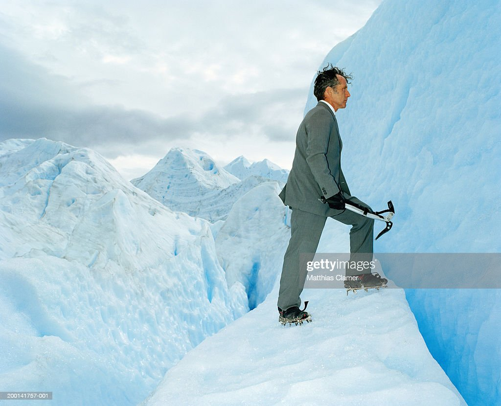 Mature businessman wearing ice cleats climbing glacier, side view : Stock Photo