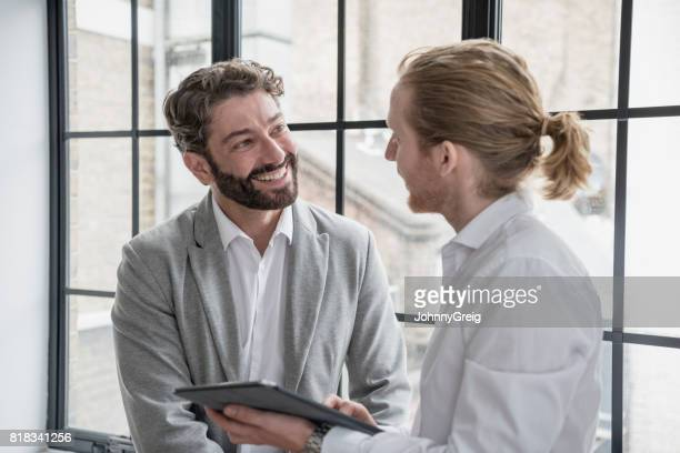 Mature businessman with beard smiling and listening to young male colleague with tablet