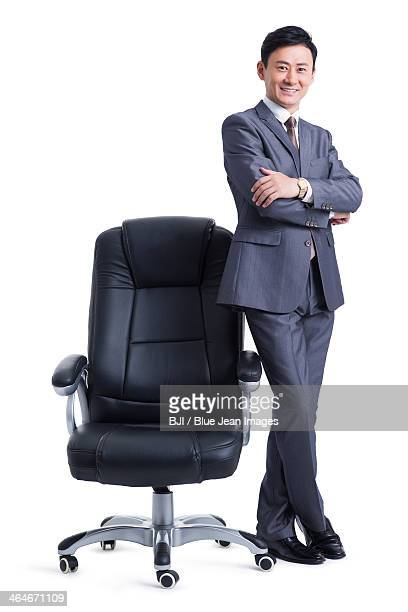 Mature businessman with boss chair