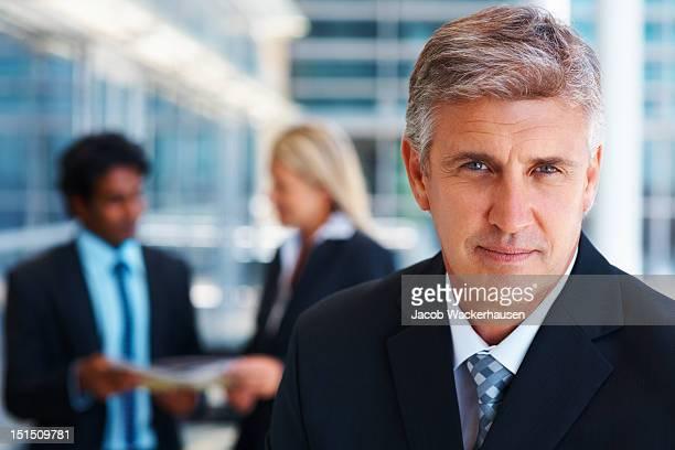 Reifer Geschäftsmann mit Kollegen im Hintergrund