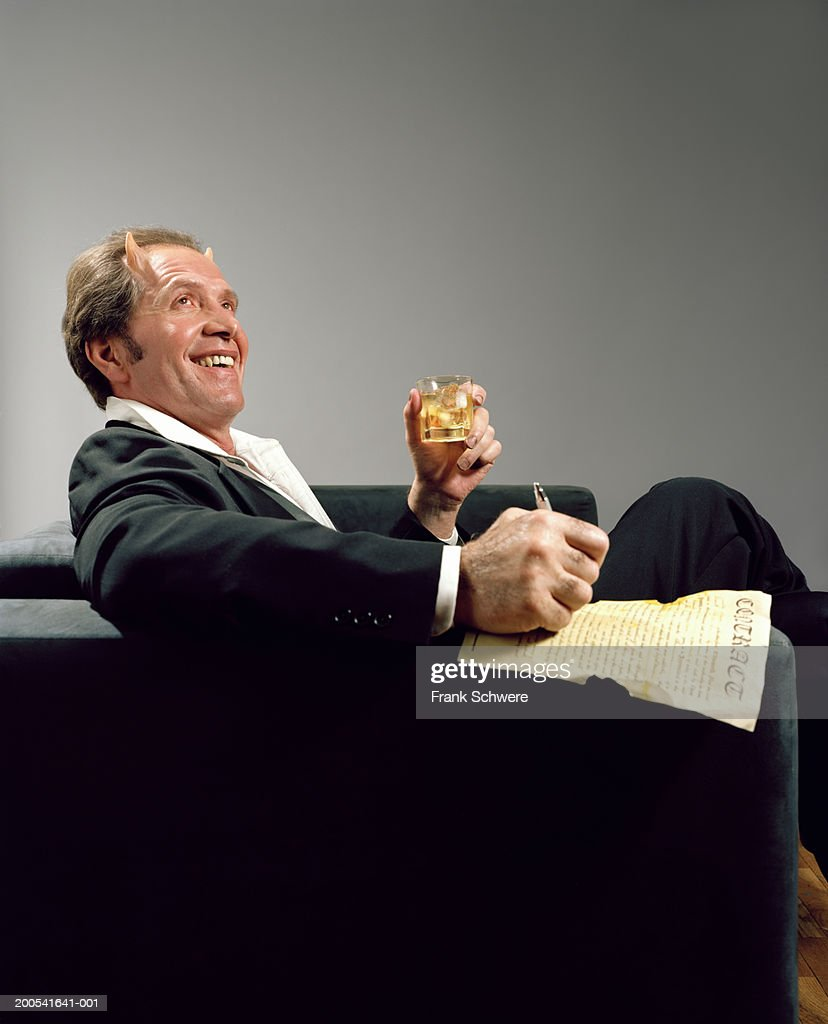 Mature businessman with devil's horns signing contract : Stock Photo