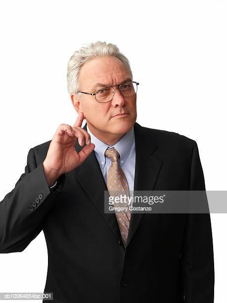 Mature businessman with finger in ear, portrait
