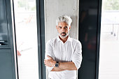 Handsome mature businessman with gray hair in the office wearing white shirt, arms crossed.