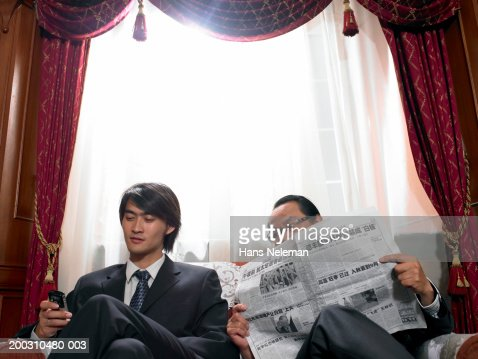 Mature businessman with newspaper looking at young man's mobile phone : Stock Photo