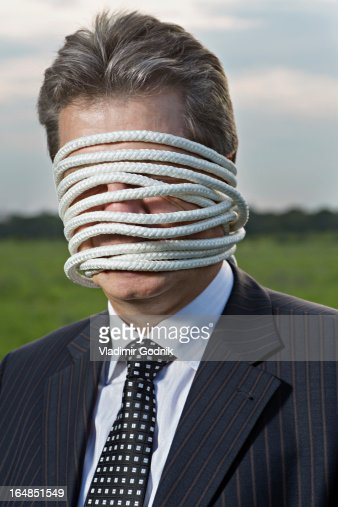 A mature businessman with rope wrapped around his face : Stock Photo