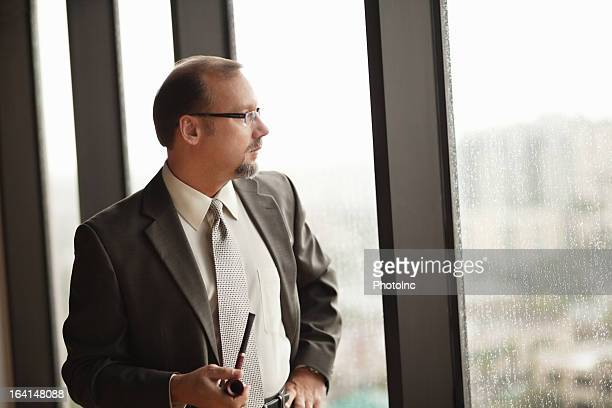 Mature Businessman With Smoking Pipe At Office
