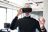 Handsome mature businessman with virtual reality goggles in the office.