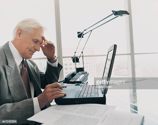 Mature Businessman Working at His Desk on a Laptop in the Office
