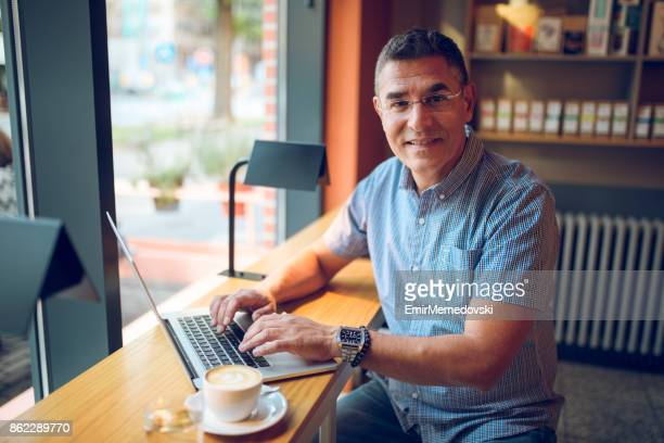 Mature businessman working on laptop in cafe