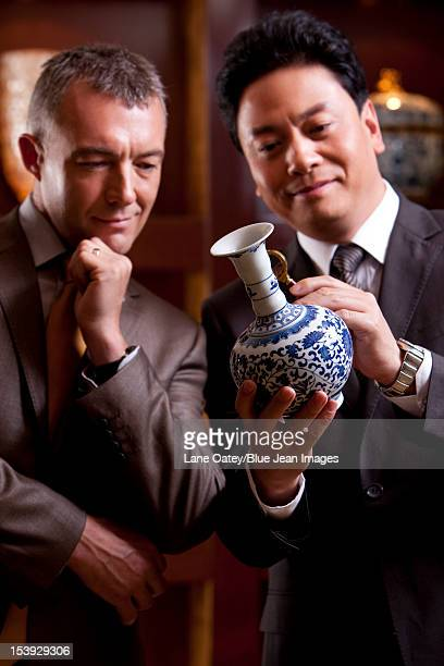 Mature businessmen admiring an antique Chinese vase