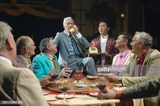 Mature businessmen at table, one standing using phone held by waiter