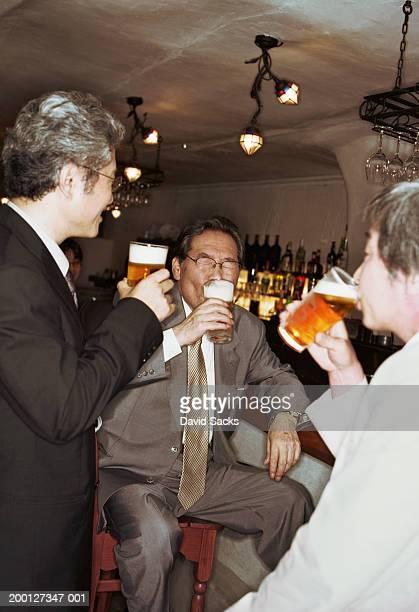 Mature businessmen drinking beer in bar