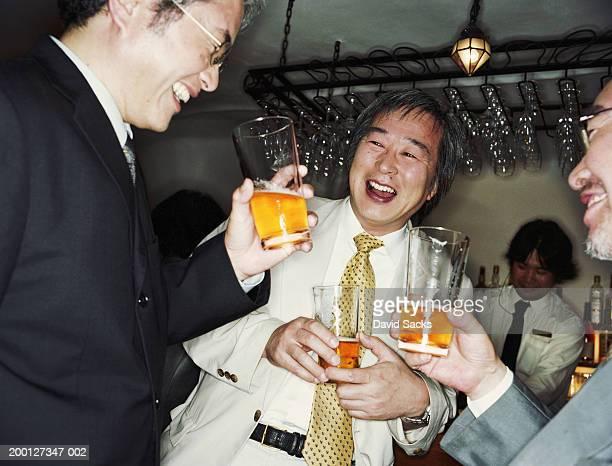 Mature businessmen laughing in bar